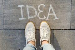 Vue d'en haut, pieds femelles avec l'idée des textes écrite sur le trottoir gris image stock