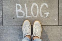 Vue d'en haut, pieds femelles avec le blog des textes écrit sur le trottoir gris photographie stock libre de droits