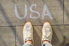 Vue d'en haut, pieds femelles avec le texte Etats-Unis écrit sur le trottoir gris image libre de droits