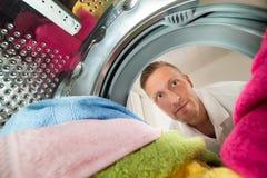 Vue d'homme de l'intérieur de la machine à laver Photographie stock