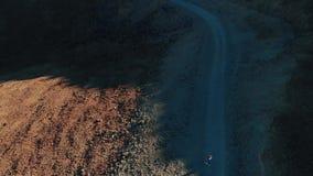 Vue d'oeil d'oiseaux La jeune fille dans des vêtements de denim court le long du chemin de trekking au volcan, parc national de T banque de vidéos