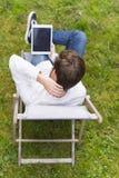 Vue d'oiseau sur penser la personne méconnaissable s'asseyant avec le comprimé Photo libre de droits
