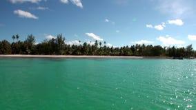 Vue d'un bateau mobile sur la plage et les palmiers de sable sur le fond de l'océan banque de vidéos