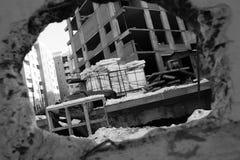 Vue d'un chantier de construction par un trou dans le mur photo stock