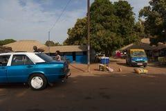 Vue d'un chemin de terre dans une rue d'un taudis dans la ville du Bissau avec des personnes entrant dans un taxi, en Guinée-Biss photographie stock
