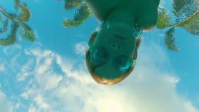 Vue d'un fond d'une piscine sur des palmiers et d'un petit enfant nageant au-dessus de la caméra banque de vidéos