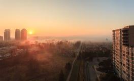 Vue d'un gratte-ciel vers les maisons urbaines pendant un sunr brumeux Photographie stock