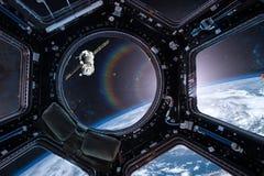 Vue d'un hublot de station spatiale sur le fond de la terre image stock
