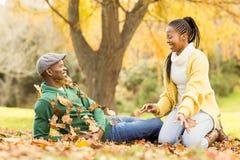 Vue d'un jeune couple de sourire dans des feuilles Photographie stock