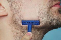 Vue d'un jeune homme barbu avec un rasoir brutal visage sur le fond bleu grands poils velus rugueux sur la peau, clos de vue de c image libre de droits