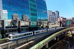 Vue d'un train voyageant sur les rails élevés du système de métro de Taïpeh par un bâtiment moderne des murs rideaux en verre sur Photo stock