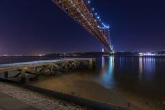 Vue d'un vieux pilier aux banques du Tage Rio Tejo avec les 25 d'April Bridge sur le backgound la nuit Photographie stock