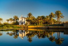 Vue d'une église avec une réflexion dans l'eau et un pont à travers la rivière dans la région d'Alboraya Valence, Espagne photos libres de droits