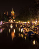 Vue d'une église et d'un canal à Amsterdam, Pays-Bas la nuit La basilique du saint Nicholas Sint-Nicolaasbasiliek avec le r images stock