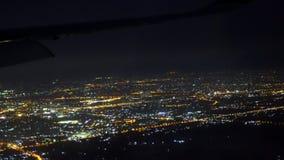 Vue d'une fenêtre du passager de l'avion Les beaux espaces ouverts de la ville ont rempli de feux de nuit L'avion banque de vidéos