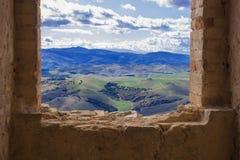 Vue d'une fenêtre ruinée sur les champs verts image libre de droits