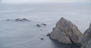 Vue d'une formation des roches en mer avec de l'eau dans le calme banque de vidéos