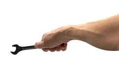 Vue d'une main du ` s d'homme jugeant la clé combinée d'isolement sur le fond blanc Photo libre de droits