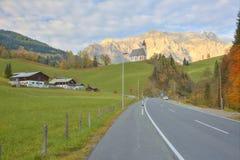Vue d'une route de campagne passant par une terre de ferme avec une église sur la colline et la montagne Hochkoenig Images libres de droits