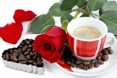 Vue d'une tasse de café avec une rose rouge et des grains de café sur le petit morceau Image stock