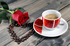 Vue d'une tasse de café sur un vieux en bois de table orné avec un RO rouge Images stock
