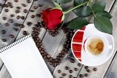 Vue d'une tasse de café sur un vieux en bois de table orné avec un RO rouge Image libre de droits
