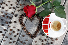 Vue d'une tasse de café sur un vieux en bois de table orné avec un RO rouge Photo libre de droits