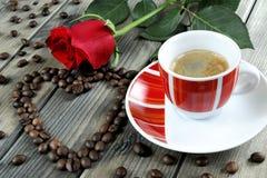 Vue d'une tasse de café sur un vieux en bois de table orné avec un RO rouge Photographie stock