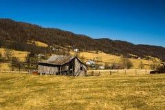 Vue d'une vieille grange en vallée bleue d'herbe photographie stock libre de droits