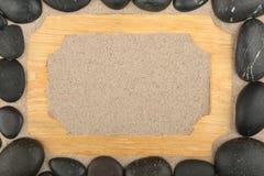 Vue de bois léger sur le sable et les pierres noires autour Avec l'espace pour le texte Images stock