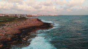 Vue de bourdon de bord de la mer rocheux avec la belle promenade de touristes piétonnière verte et vagues énormes de mer qui se h banque de vidéos