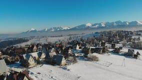 Vue de bourdon des cottages et des maisons sur le terrain neigeux en montagnes avec le soleil lumineux clips vidéos