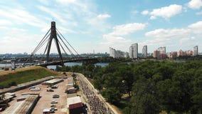 Vue de bourdon de rive avec le grand pont concret et groupe de cavaliers de vélo croisant par le parc de touristes récréationnel  banque de vidéos