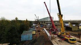 Vue de bourdon de secteur de construction de pont avec deux grues chaussée et champ voisins banque de vidéos