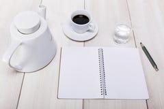 Vue de bureau avec le carnet et le crayon, et pot frais de café et Photos stock