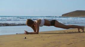 Vue de côté de belle femme sportive en position de planche sur la plage pendant le coucher du soleil clips vidéos