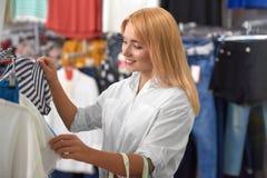 Vue de côté de blonde recherchant de nouveaux vêtements dans le magasin photos libres de droits