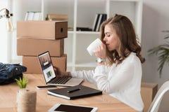 vue de côté de café potable de femme d'affaires tout en travaillant sur l'ordinateur portable image libre de droits