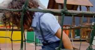 Vue de côté d'écolière de métis jouant dans le terrain de jeu d'école un jour ensoleillé 4k banque de vidéos