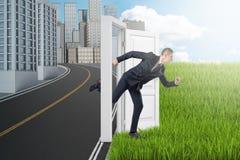 Vue de côté d'homme d'affaires fonctionnant de la ville moderne au champ vert par la porte seul se tenant entre eux sans le mur image stock