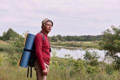 Vue de côté d'homme d'eldery avec le sac à dos et la couverture bleue, apprécier d'admirer la vue majestueuse de la rivière tout  photos stock