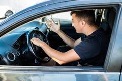 Vue de côté d'homme fâché dans le costume conduisant une voiture et des signaux sonores image stock