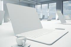 Vue de côté d'ordinateur portable blanc vide sur la table Photographie stock libre de droits