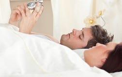 Vue de côté d'un homme réglant son horloge d'alarme Image libre de droits