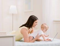 Vue de côté de la mère et de la chéri jouant avec l'ordinateur portatif Images stock