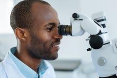Vue de côté de dentiste regardant dans la lentille de microscope Photo libre de droits