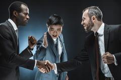 vue de côté des associés multi-ethniques serrant la main au collègue se tenant tout près photographie stock libre de droits