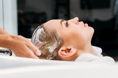 vue de côté des cheveux de lavage de coiffeur pour le client image libre de droits