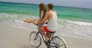 Vue de côté des couples caucasiens montant une bicyclette sur la plage 4k banque de vidéos