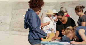 Vue de côté des volontaires divers se préparant au nettoyage de plage sur la plage 4k banque de vidéos